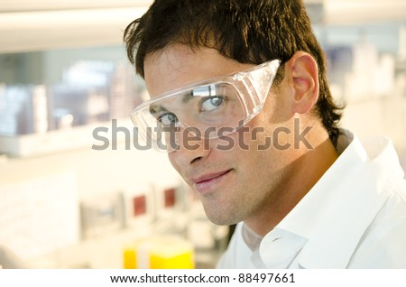 Portrait of a smiling young researcher inside his laboratory - stock photo