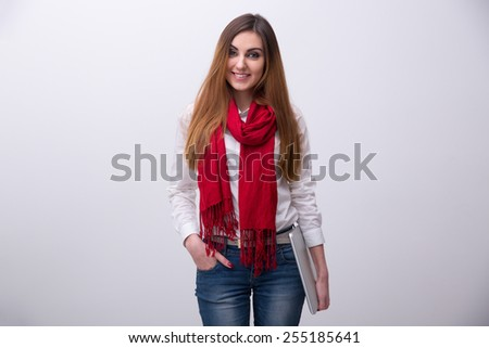 Portrait of a smiling young student standing with laptop over gray background - stock photo