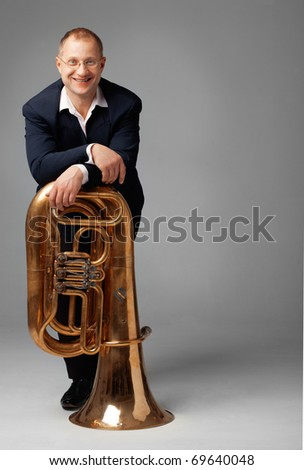 Portrait  of a  smiling young tubaist with his instrument - stock photo