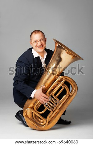 Portrait  of a  smiling young tubaist with his instrument