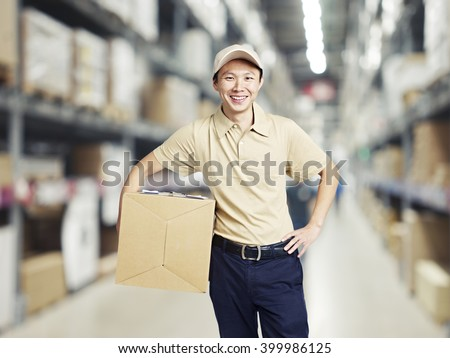 portrait of a smiling young warehouse worker working in a cash and carry wholesale store. - stock photo