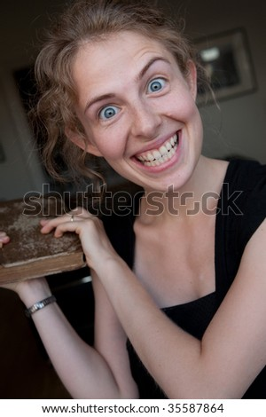 portrait of a smiling young woman beating with a book; before modern minimalistic interior design fo a library - stock photo