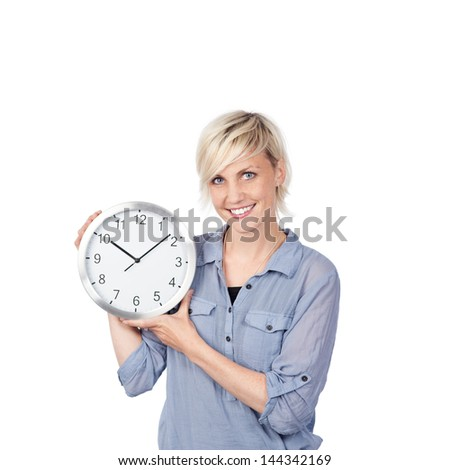 Portrait of a smiling young woman holding a clock against white background