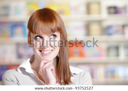 portrait of a  smiling young woman in a library - stock photo