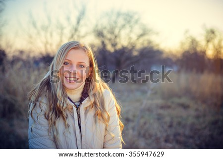 Portrait of a smiling young woman looking at the camera, with blue eyes and blond hair. Shot outdoors in a cold autumn day with natural background.