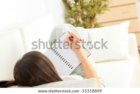 Portrait of a smiling young woman lying on sofa and writing documents - stock photo
