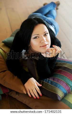 Portrait of a smiling young woman lying on the floo - stock photo