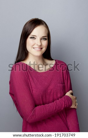Portrait of a smiling young woman on gray studio background, wearing pink purple top with long brunette hair