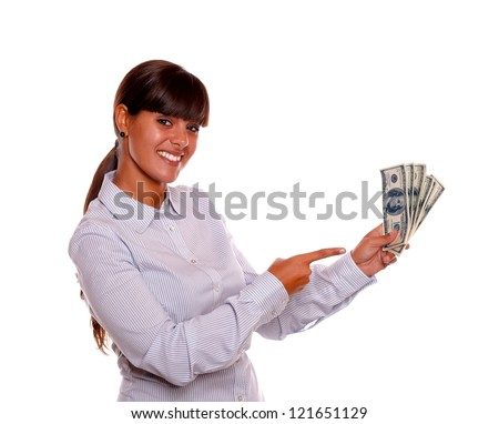 Portrait of a smiling young woman pointing and holding cash money standing over white background - stock photo
