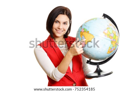 Portrait of a smiling young woman pointing finger at globe on white isolated background