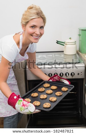 Portrait of a smiling young woman putting a tray of cookies in the oven at kitchen - stock photo