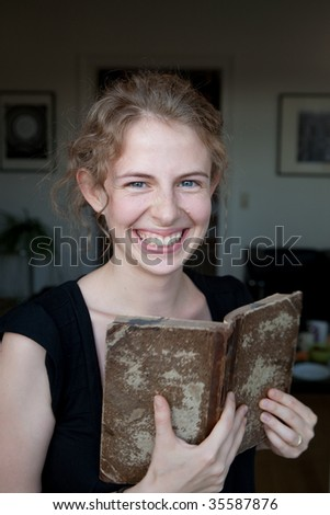 portrait of a smiling young woman reading a book as a student, before modern minimalistic interior design fo a library - stock photo
