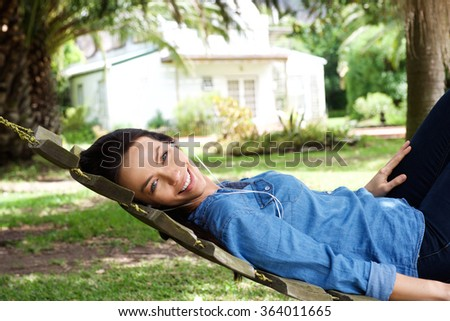Portrait of a smiling young woman relaxing outside listening to music with earphones - stock photo