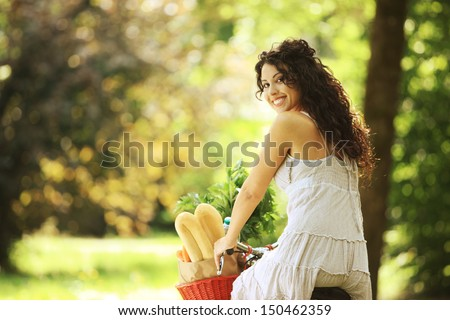 Portrait of a smiling young woman riding bicycle with groceries in basket - stock photo