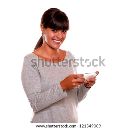 Portrait of a smiling young woman sending message by cellphone looking at you on isolated background - stock photo