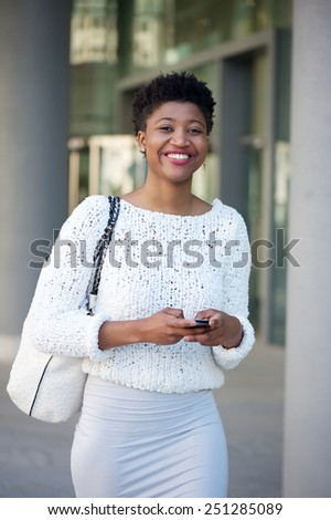 Portrait of a smiling young woman sending text message int he city - stock photo