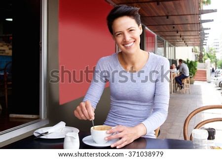 Portrait of a smiling young woman sitting at cafe enjoying coffee - stock photo