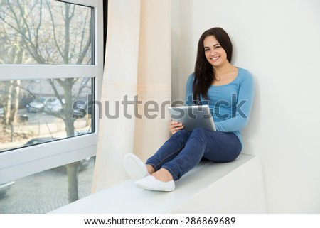 Portrait Of A Smiling Young Woman Sitting Near Window Using Digital Tablet - stock photo