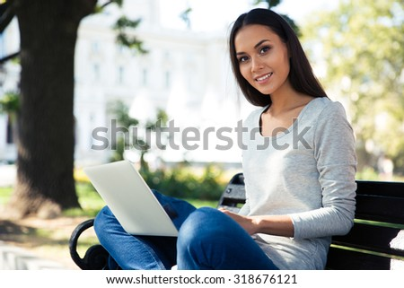 Portrait of a smiling young woman sitting on the bench and using laptop computer outdoors. Looking at camera