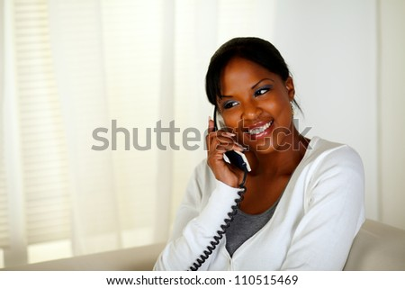 Portrait of a smiling young woman speaking on phone while sitting on couch at home indoor - stock photo