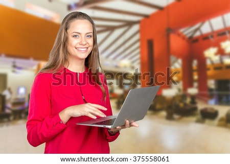 Portrait of a smiling young woman standing with laptop