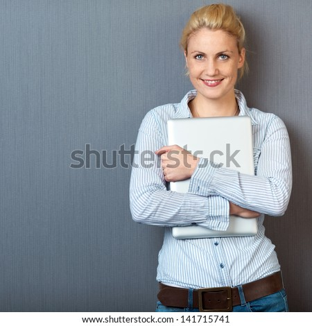 Portrait of a smiling young woman standing with laptop against gray background - stock photo
