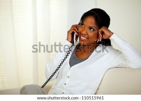 Portrait of a smiling young woman talking on phone while sitting relaxed on sofa at home indoor - stock photo