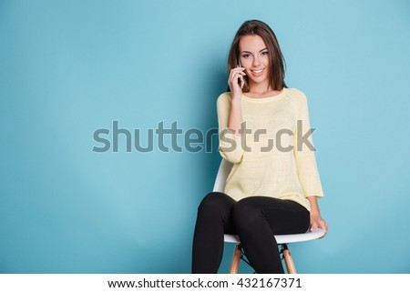 Portrait of a smiling young woman talking on the phone and looking at camera isolated on a blue background - stock photo