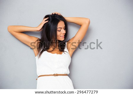 Portrait of a smiling young woman touching her hair over gray background