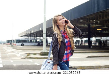 Portrait of a smiling young woman traveling with bag and mobile phone