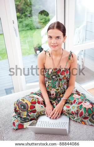 Portrait of a smiling young woman using a laptop while sitting on couch - stock photo