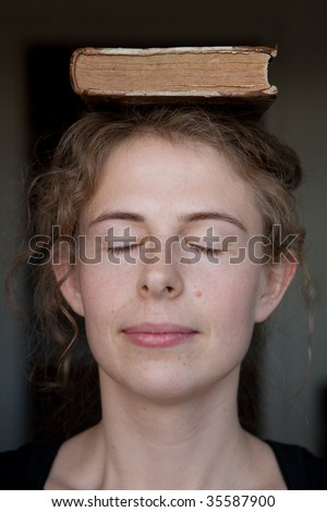 portrait of a smiling young woman with an old book upon her head and the eyes closed - stock photo