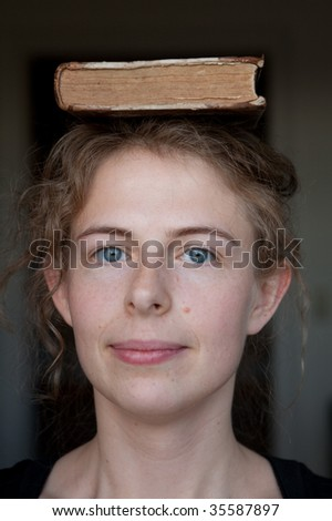 portrait of a smiling young woman with an old book upon her head (natural beauty) - stock photo