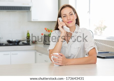 Portrait of a smiling young woman with coffee cup using landline phone in the kitchen at home - stock photo