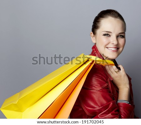 Portrait of a smiling young woman, with long brunette hair, on gray studio background, in luxury clothes, with bright shopping paper bags  - stock photo