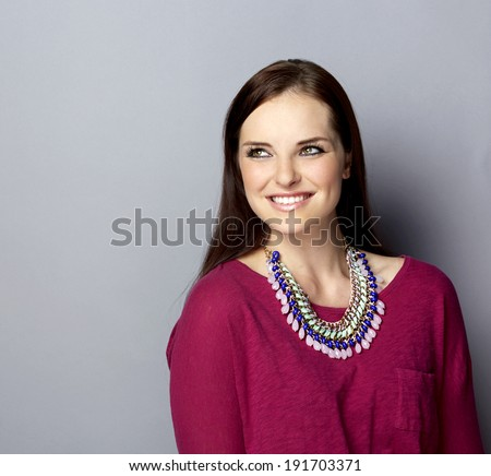 Portrait of a smiling young woman, with long brunette hair, on gray studio background, wearing pink purple top and bright statement necklace - stock photo