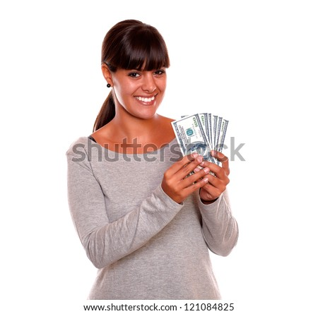 Portrait of a smiling young woman with money on grey dress looking at you standing over white background