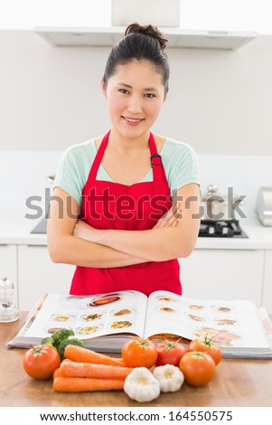 Portrait of a smiling young woman with recipe book and vegetables in the kitchen at home