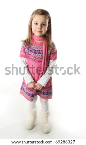 Portrait of a smilng adorable preschool girl wearing a knit pink dress and scarf - stock photo