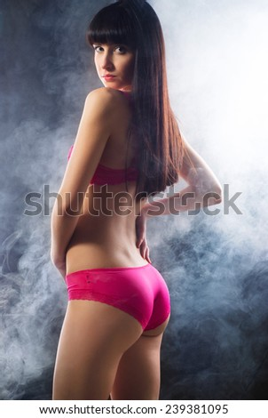 Portrait of a smoking hot sexy fit young woman posing in pink lingerie on dark background  - stock photo