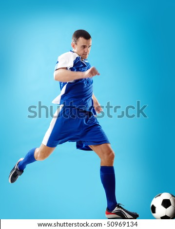Portrait of a soccer player with ball on a blue background - stock photo