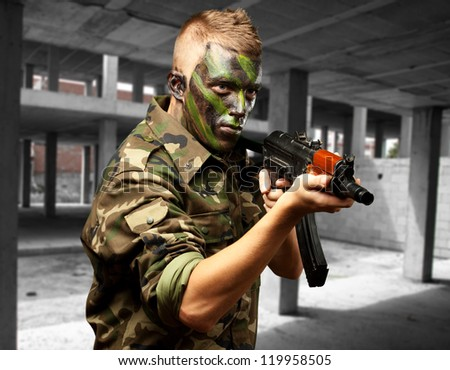Portrait Of A Soldier Aiming With Gun at an old building - stock photo