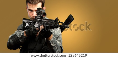 Portrait Of A Soldier Holding Gun against an orange background - stock photo