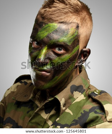 portrait of a soldier with camouflage painting against a grey background