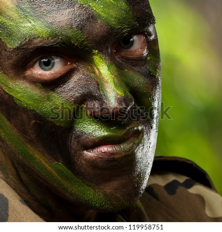 portrait of a soldier with camouflage painting against a nature background - stock photo