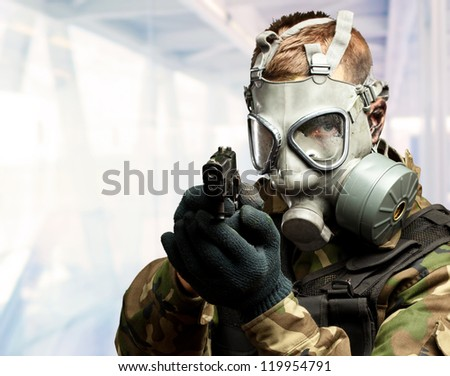 Portrait Of A Soldier With Gas Mask Aiming With Gun, indoor - stock photo