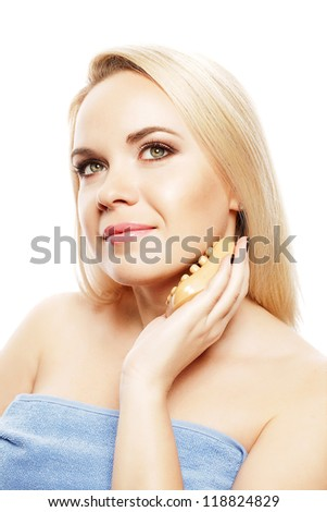 Portrait of a spa woman. Beautiful blonde girl after bath touching her face with a special scrub soap. Perfect skin. Skincare. Young skin. Studio shot - stock photo