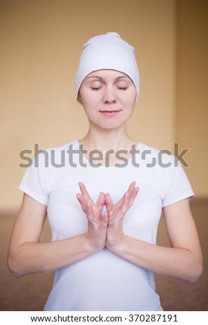 Portrait of a spiritual young woman doing yoga mudra lotos - stock photo