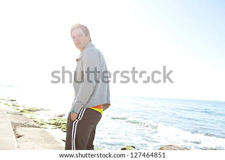 Portrait of a sports man walking along the sea front on the sea edge, turning to look at camera against a blue sky.