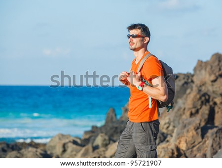 Portrait of a sports young man with backpack. in the background of the sea - stock photo